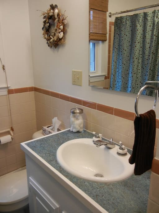 Main bathroom with original tiling and tub from 1950s. New Marmoleum flooring and tall vanity.
