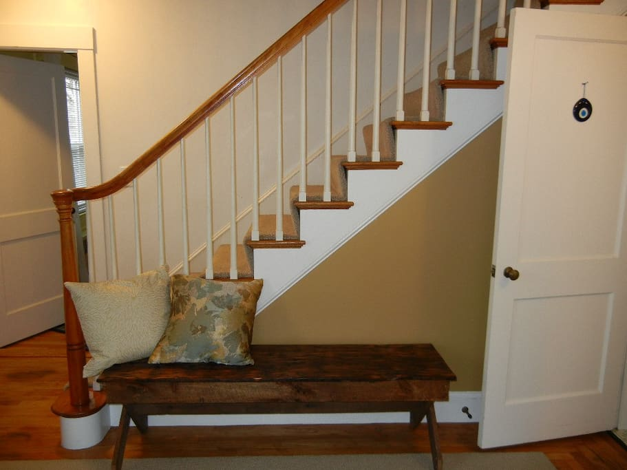 Reclaimed wood bench near stairs is made from roof of a Maine barn (200 yrs old, we're told). Door on right goes to kitchen. Doors on left lead to library-office.