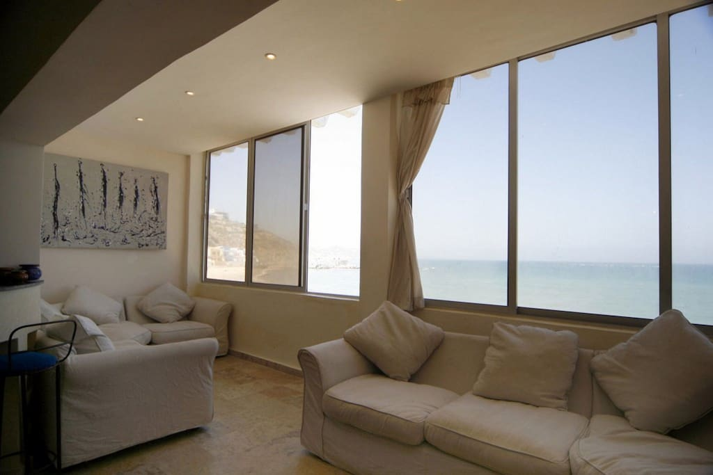 Living room with panoramic windows overlooking the beach and sea.