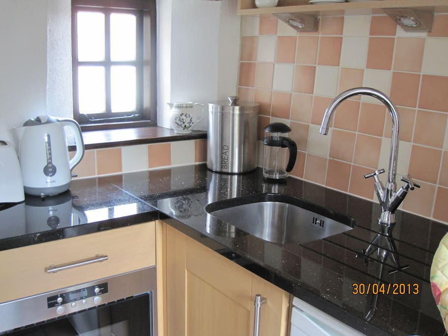 Kitchen with sink, marble work surface, microwave, cupboards