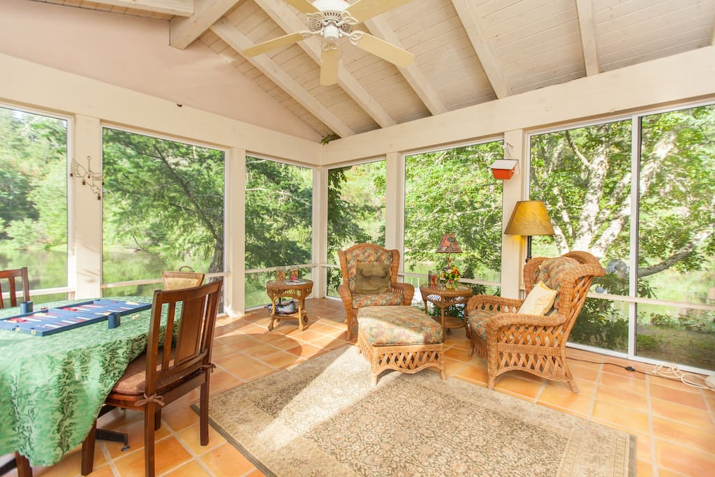 Fully screened porch overlooks the lake, perfect for dining or relaxing.