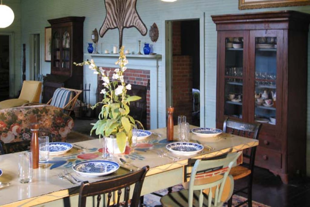 The dining area has hand-painted table and chairs and is next to the kitchen. Living area has fireplace and piano.