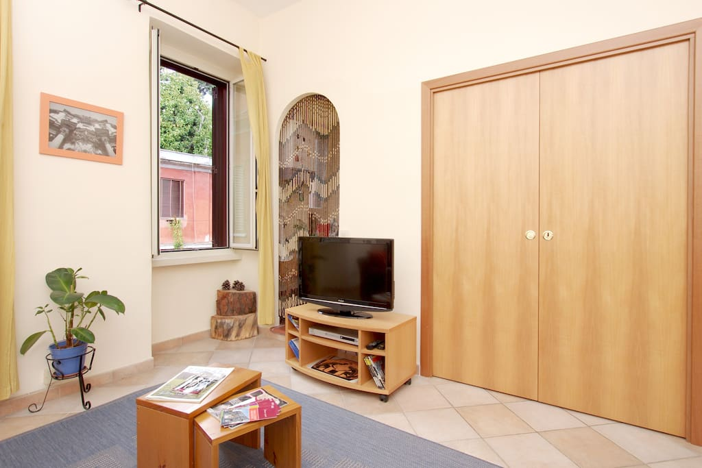 the living room, the small table and the kitchen with the wooden sliding doors closed
