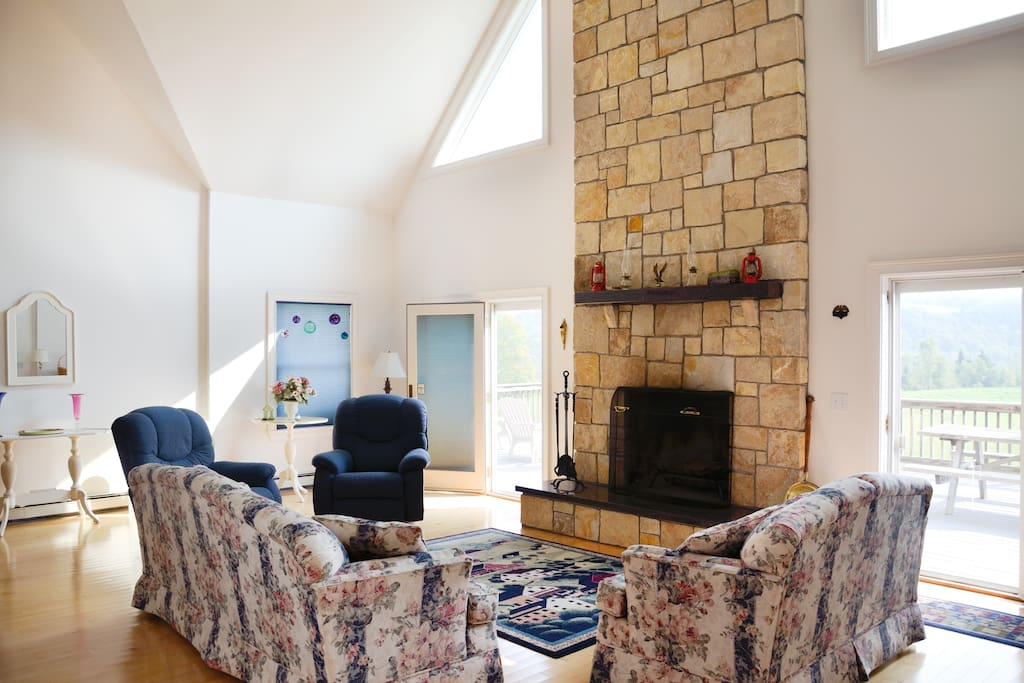 Family room with large fire place facing front view and adjacent to the dining room