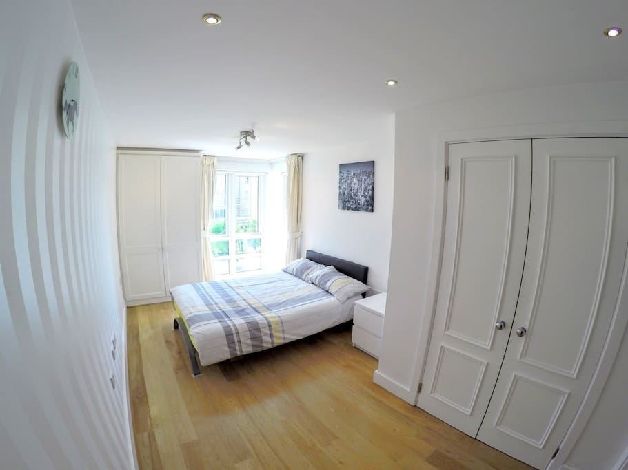 Your spacious bedroom with large built-in wardrobes and direct river views over Greenwich.