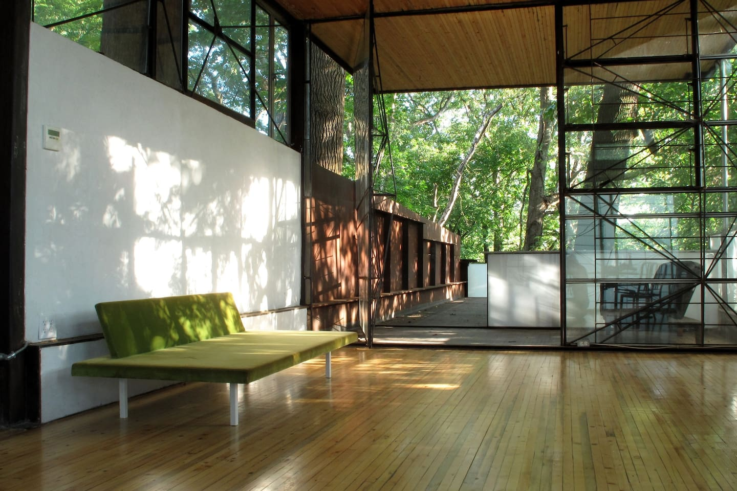 living area with giant glass door to tree shaded deck shown open-
