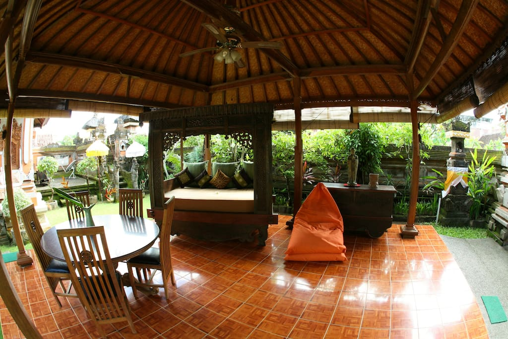 Breezy Outdoor Pavillion with Dining area , Opium day bed, all in a tropical garden setting
