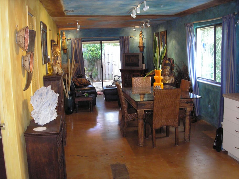 View from mid-kitchen to the patio door.  Acid-stained concrete floors are cool.  Balinese/Thai furniture with leather furniture.