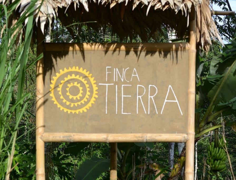 Finca Tierra's sign is made in the traditional way of building local houses out of mud and bamboo with a leaf thatch roof.