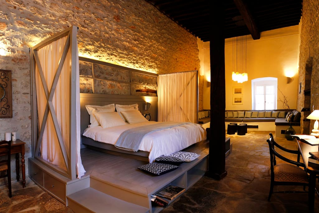 Main hall with One queen- size wooden bed with wide wooden bedhead and a view to the square