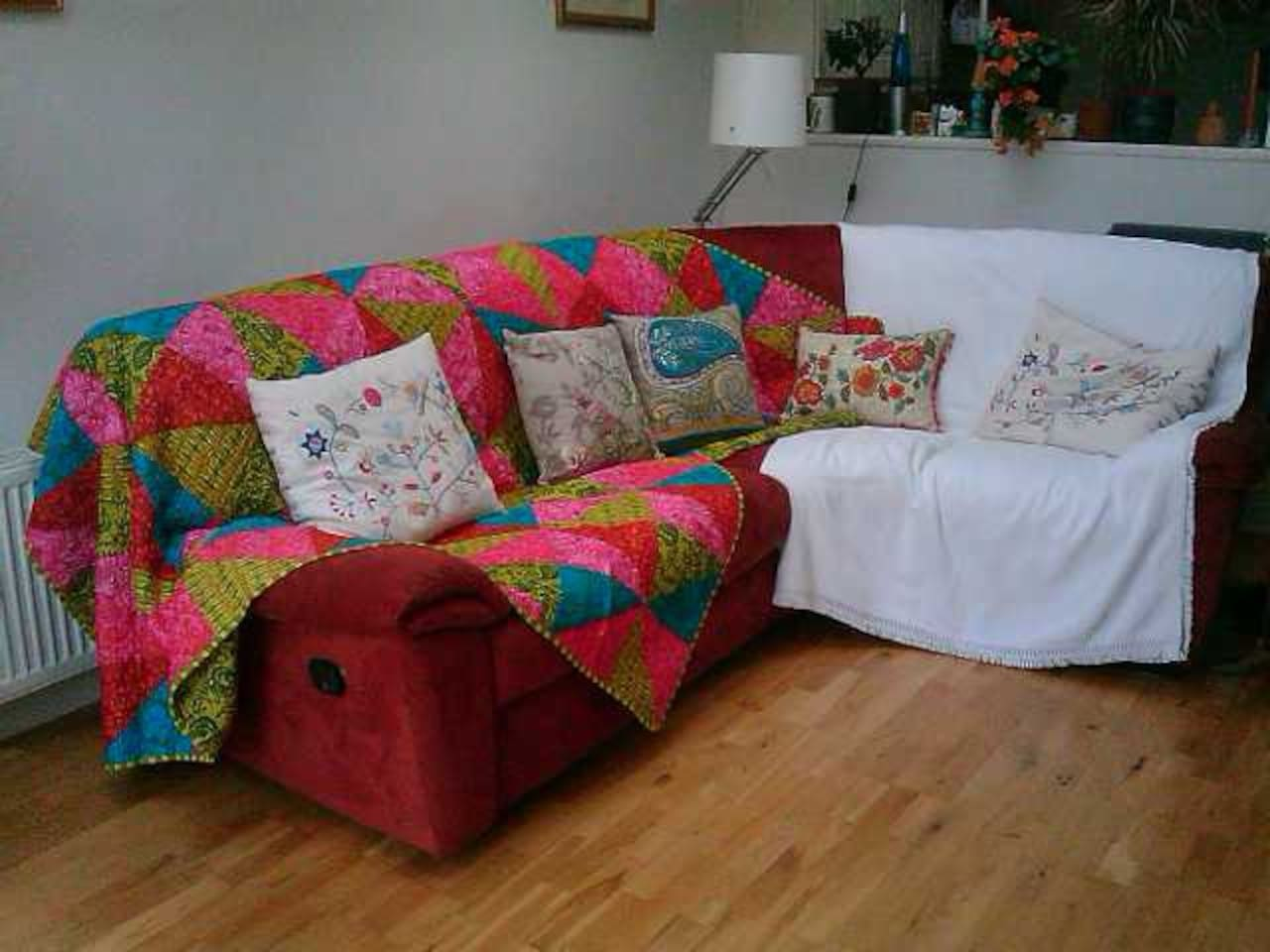 Living room with very comfortable sofa, not old and tatty, excellent condition, covered lovingly to protect it from any spills