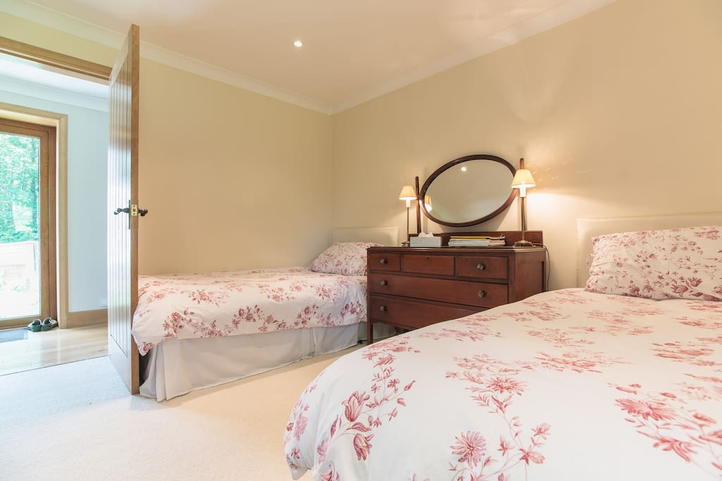 The Lomond twin room with private bathroom, views to farmland and patio doors from hallway to garden