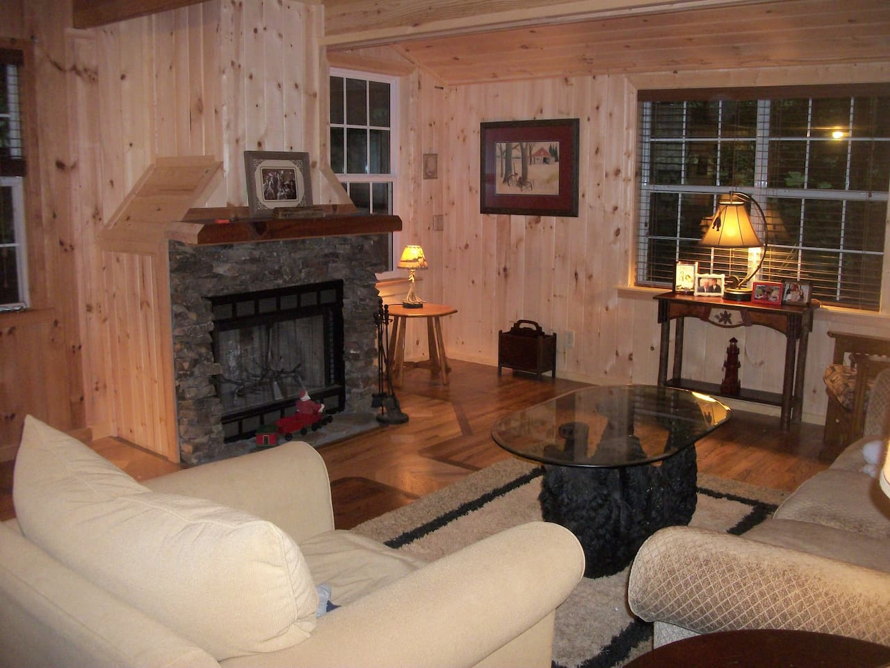 A comfortable living room with fireplace, TV/DVD, and rustic cabin decor.