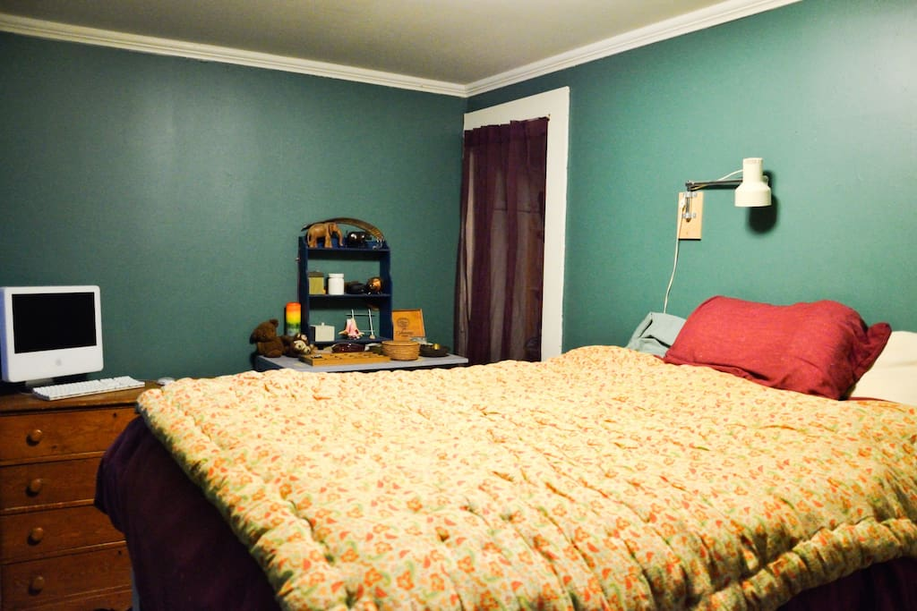 Bedroom is dark and cozy and has a platform bed.