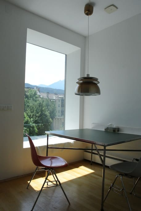 dining area view to a green courtyard and mountains