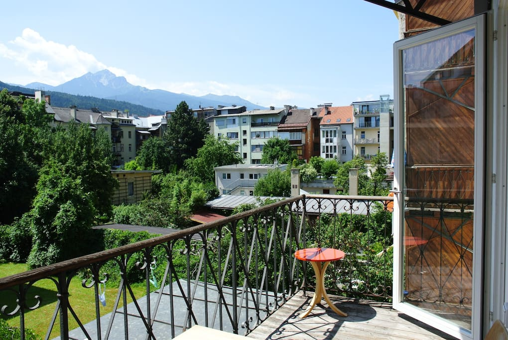 south side balcony view to a green courtyard and mountains