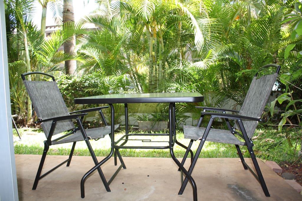 Your private patio awaits, shaded by palms and plumeria trees