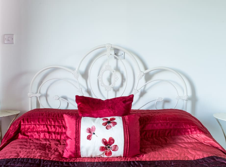 A white-painted wrought iron bed with intricate details supports a bespoke pocket-sprung mattress conducive to a great night's sleep.
