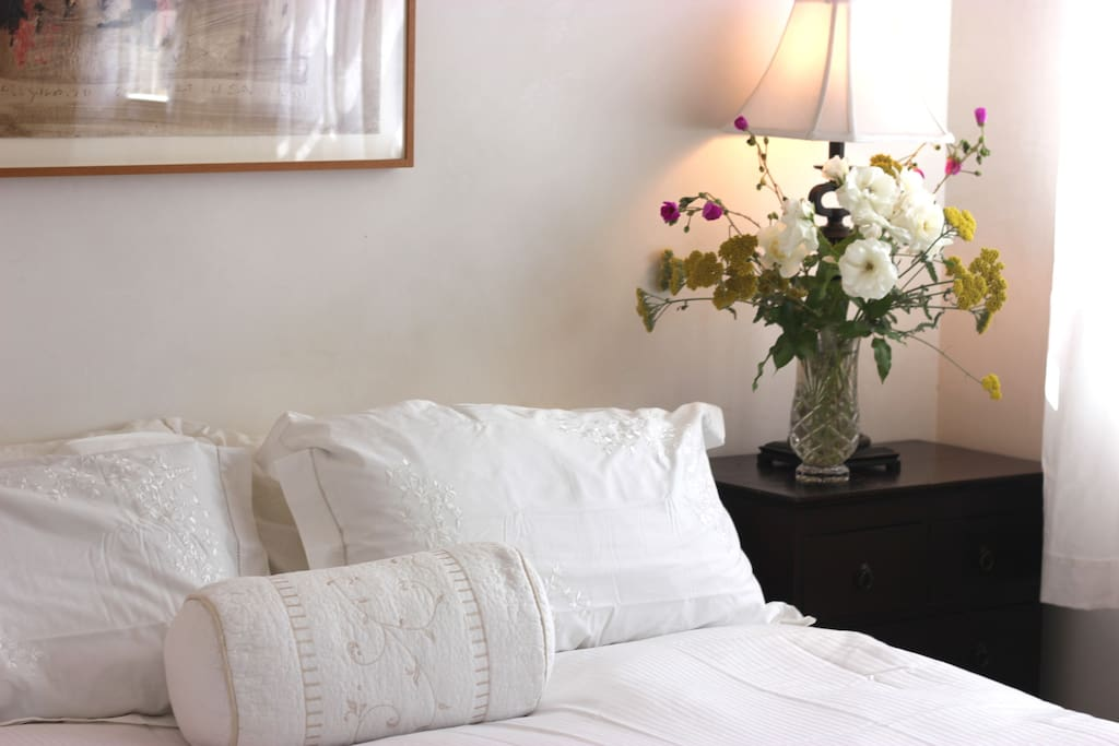 Beautiful linens in the very sunny bedroom with King bed; fresh flowers from the garden.