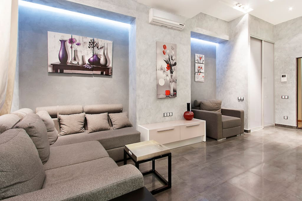 Entertainment area with sofa, coffe table, flat screen TV and airconditioner.