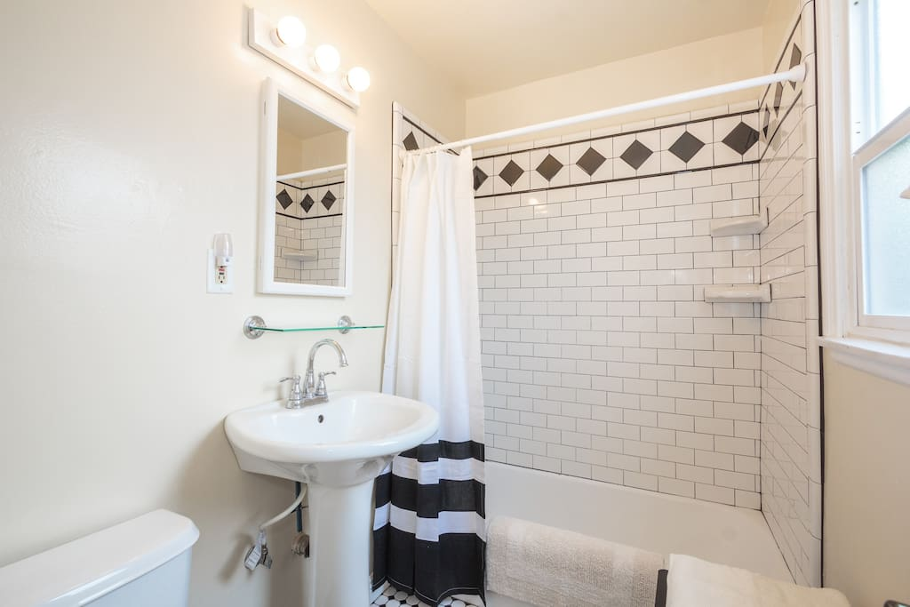 Bathroom with shower/tub featuring classic subway tiles, tall shower head, and built-in shelves to store your shower items.
