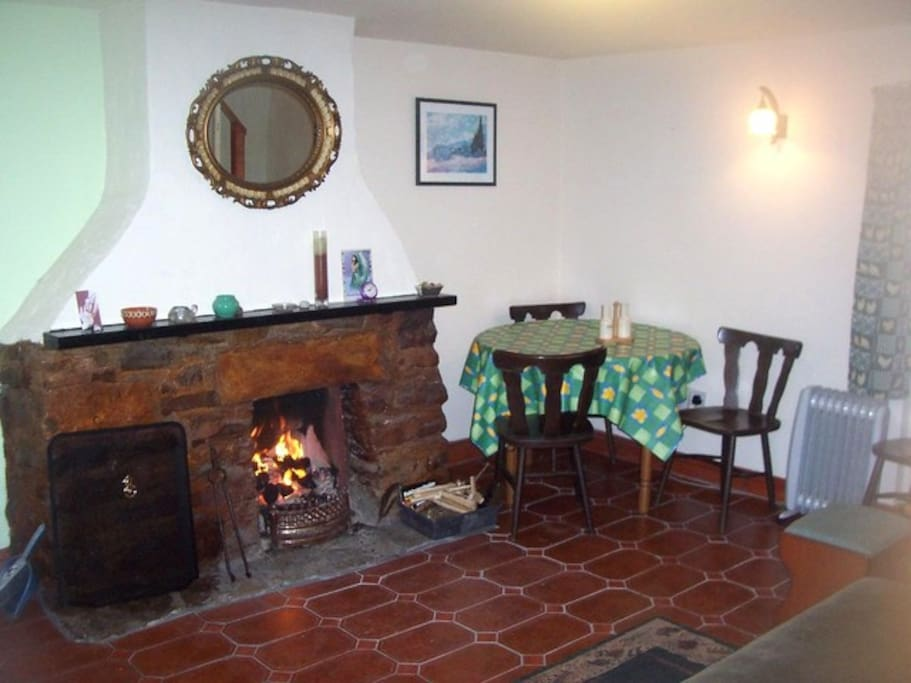 Cosy Lounge / Living Room with 'open fireplace' and dining area. Burn wood, peat, coal etc.