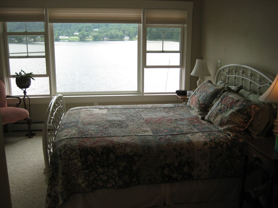 Guest room with queen bed, lake views and shower/tub bathroom.