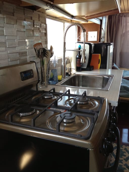 Functional kitchen includes stainless gas range oven, microwave, fridge, coffeemaker and pull down faucet