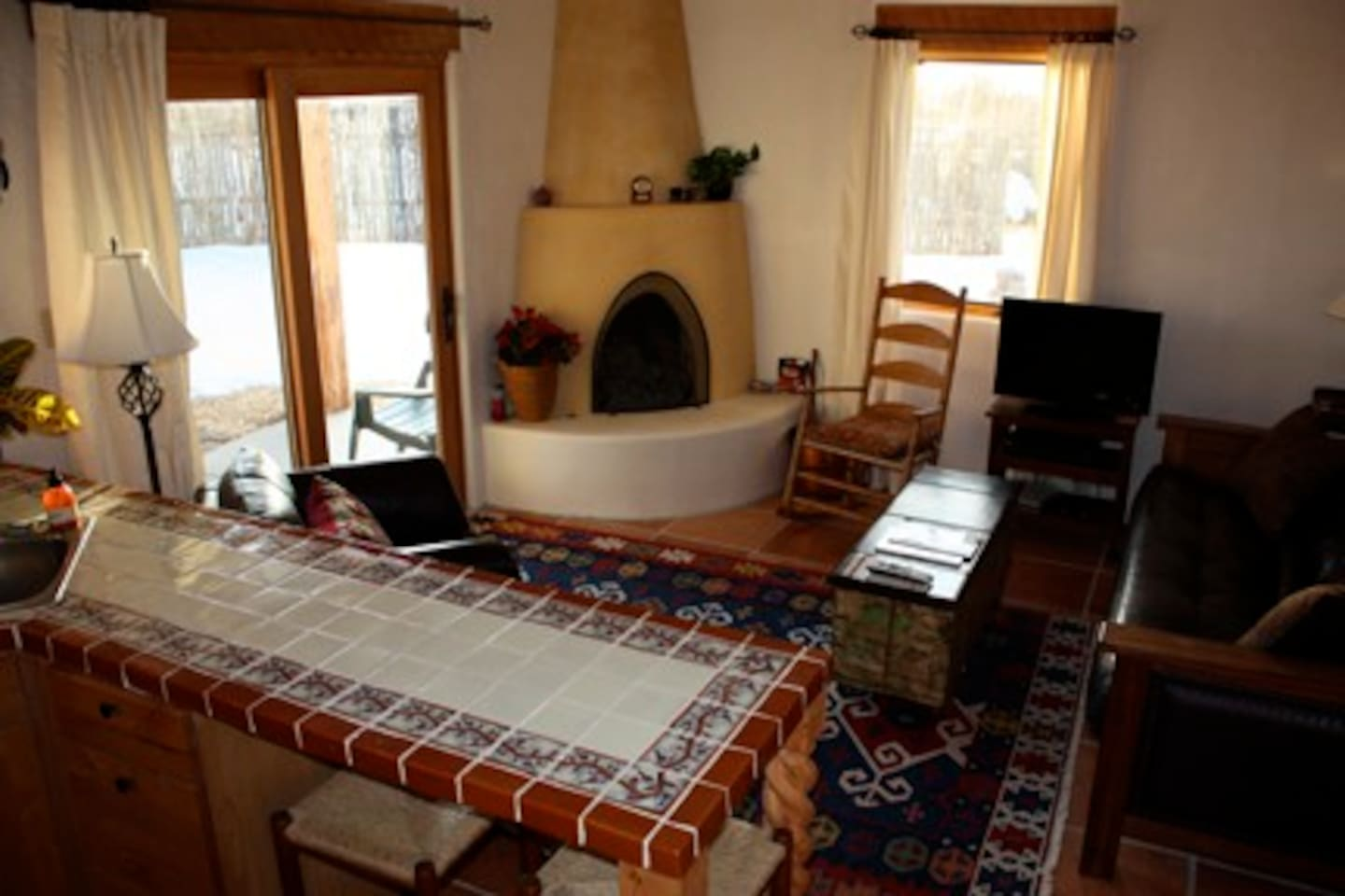 Living room with kiva fireplace - futon on right. Slider out to private yard on left.