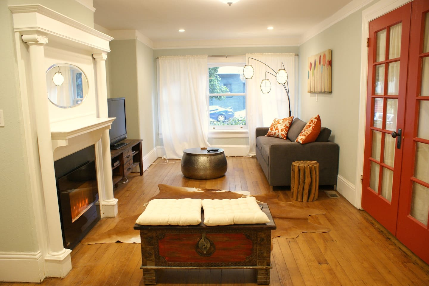 Living room with electric fireplace and bedroom doors to the right.