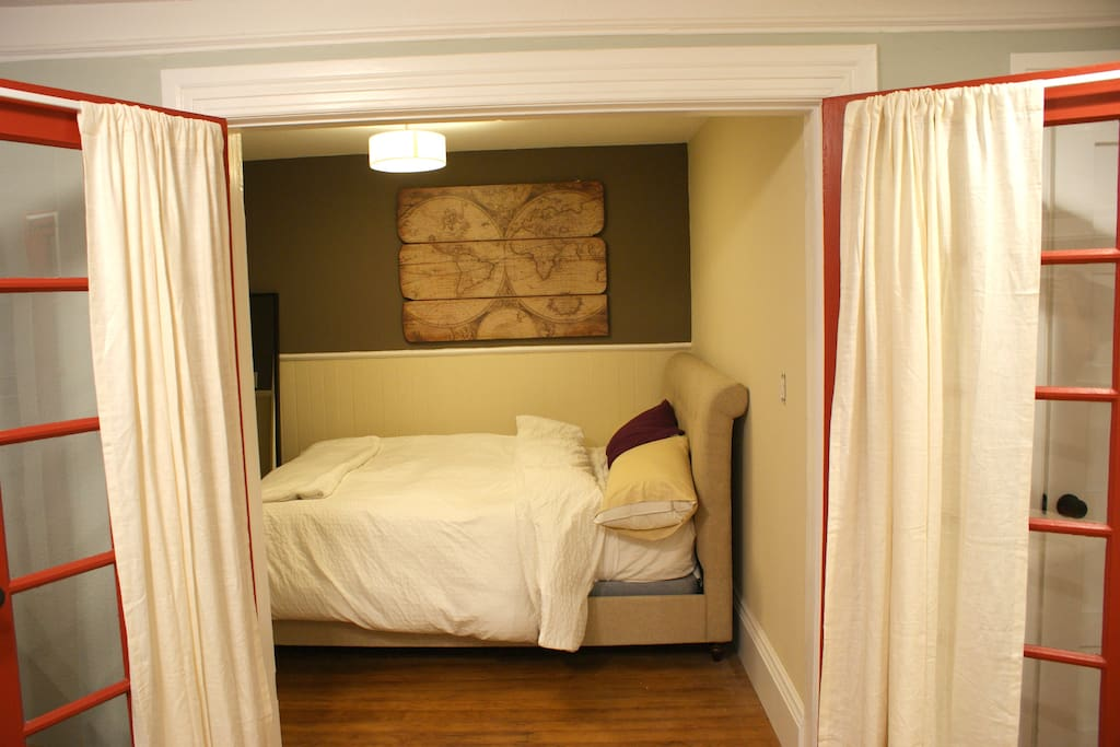 Queen size bedroom with curtained french doors.