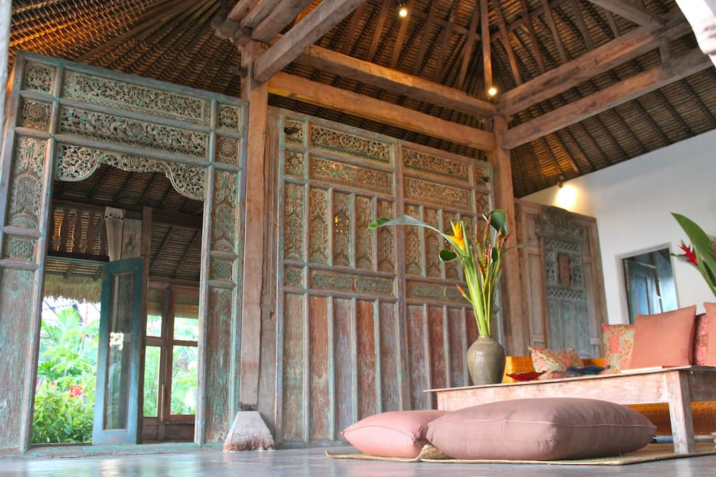 View to antique teak joglo structure and Javanese carved panels.