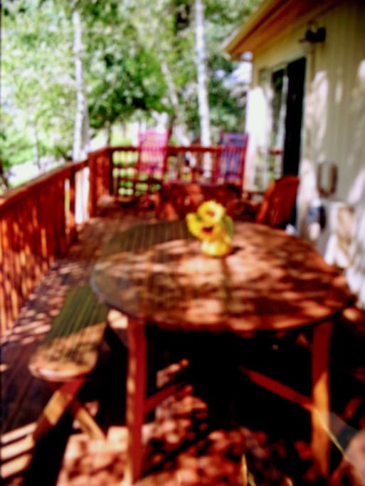 View deck surrounded by Aspen with cedar dining set for six and two red rockers in back section.