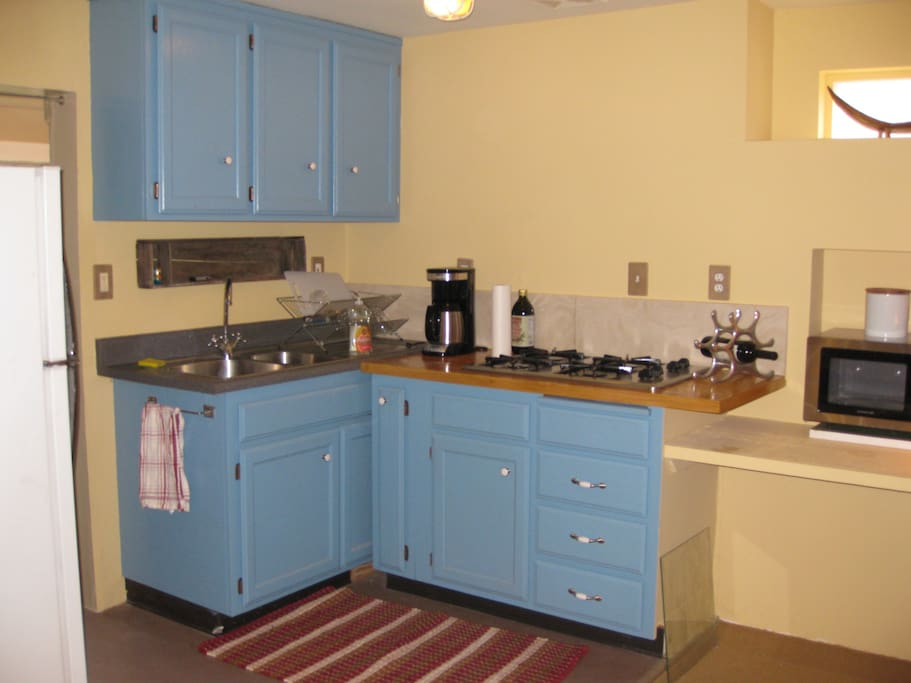 kitchen with gas range, microwave, coffee maker, toaster, fridge.
