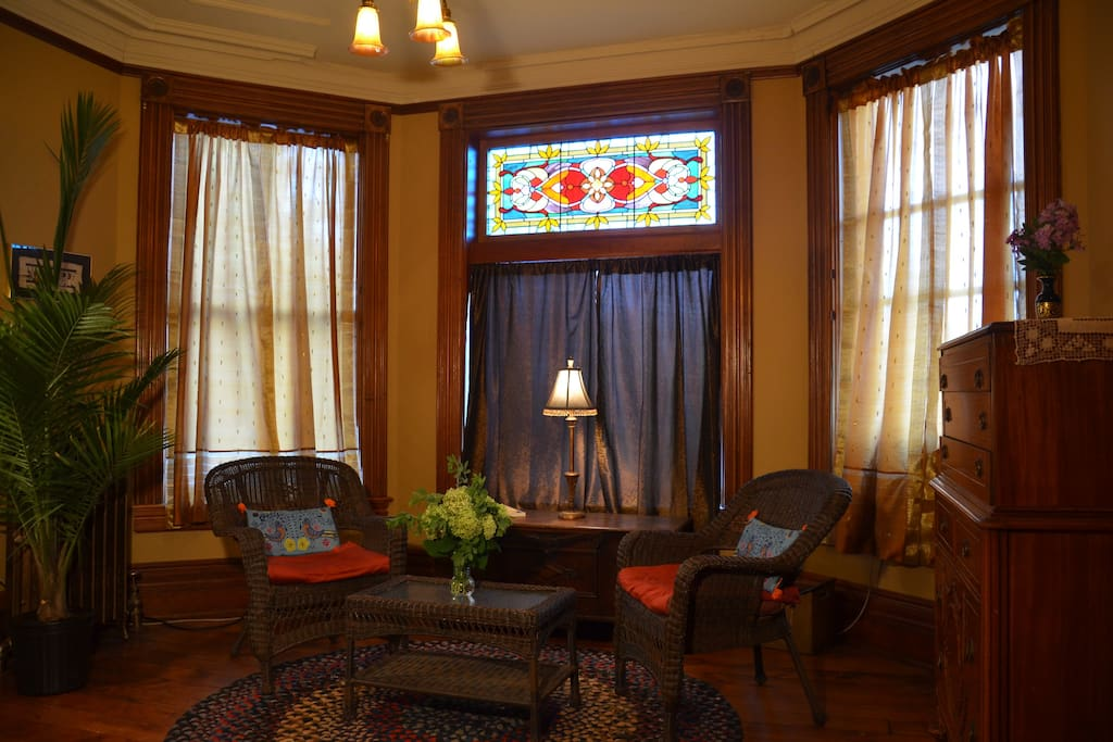 Comfortable seating area with access to upper deck.  Gorgeous original stained glass window.
