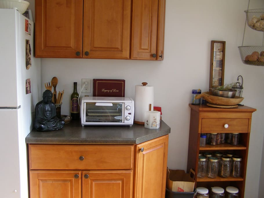 Refrigerator, slate counters and custom cabinets, toaster oven and the Buddha presiding
