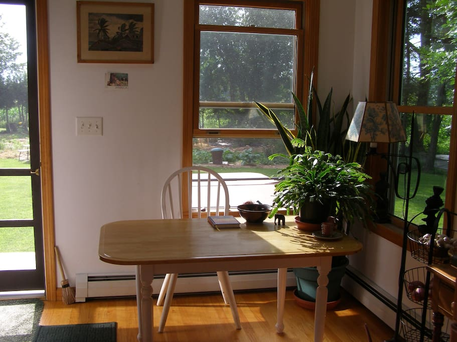 Dining area in kitchen with Christmas cactus by door with lots of light streaming in & sunsets