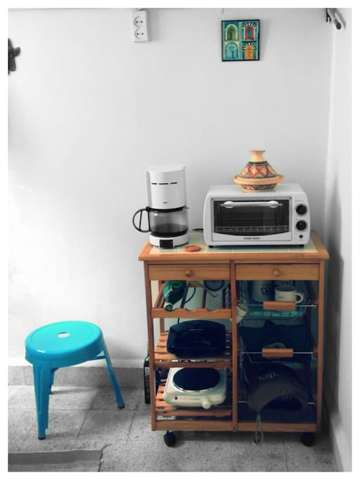 The kitchenette includes a mini fridge, filter coffee machine, and an electric hub.