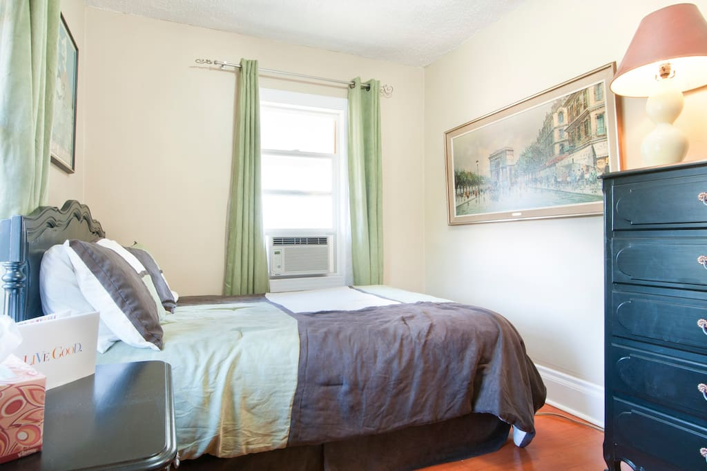 The main guest bedroom - just like you've stepped into Paris! A window AC unit, double bed, 3 dressers, immediately adjacent to the main bathroom