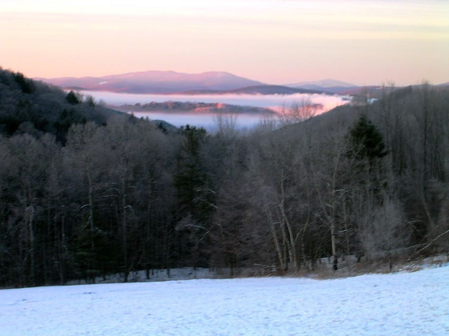 Winter sunrise over the mountains with Suicide Six ski hill in South Pomfret lit up on right