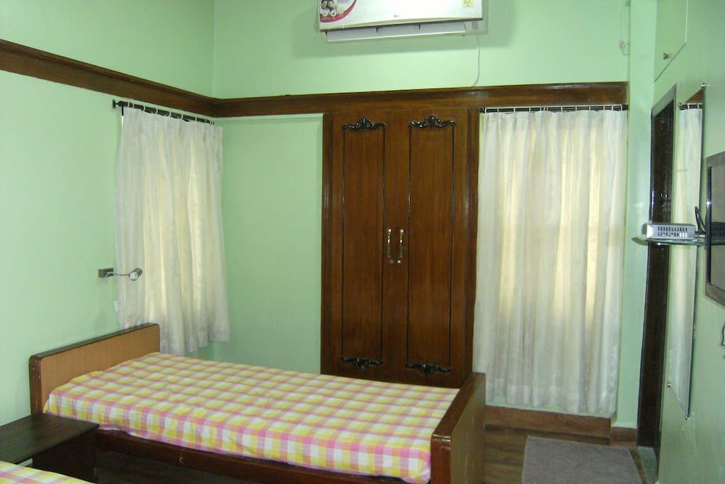 Room with wardrobe, TV, mini fridge. work table and tea/coffee maker