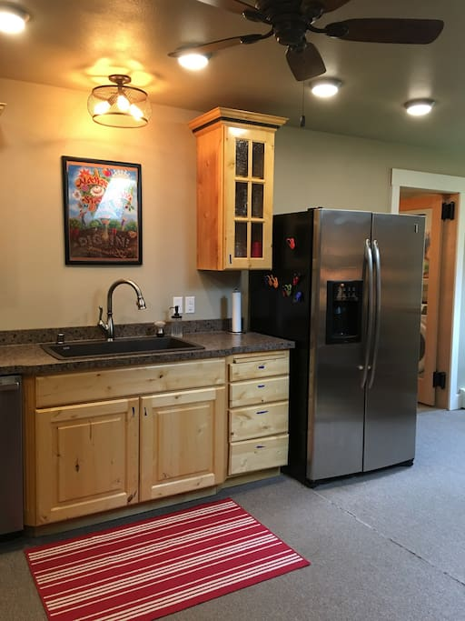 Full sized side by side refrigerator and full sized sink.