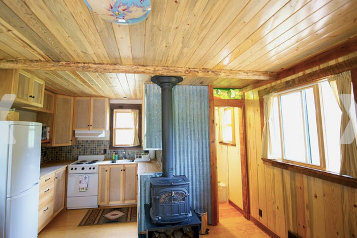 Full kitchen (micro, coffee maker and toaster hidden behind fridge) with all cooking basics provided. Firewood provided. Electric heat. Custom tile through out.