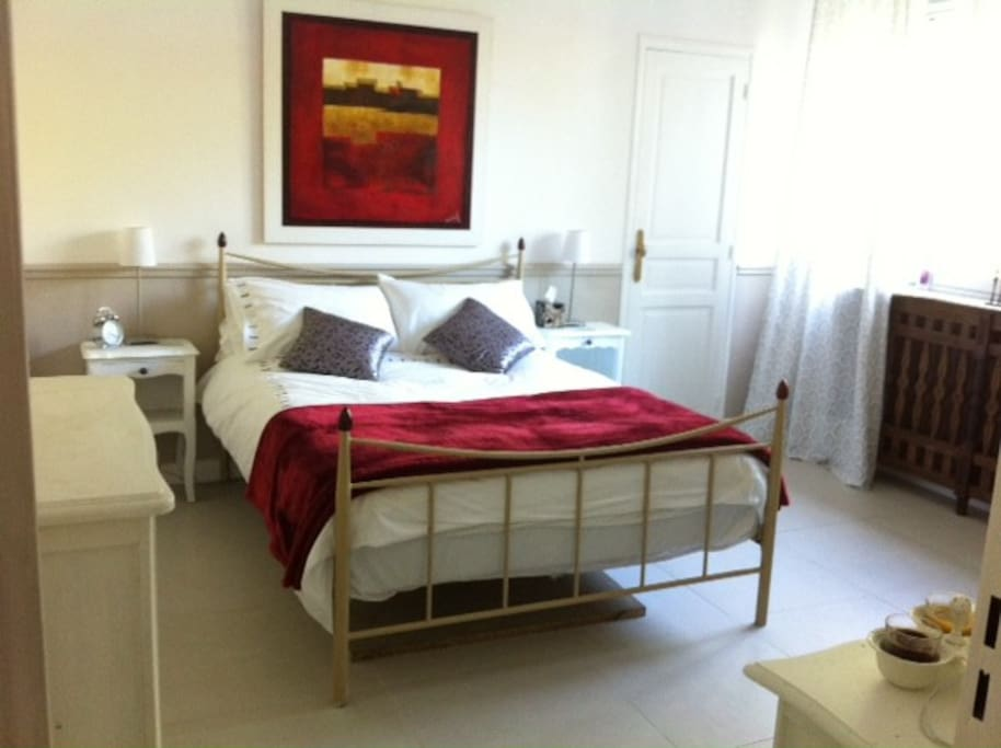 Double bed with reading lamps, chest of drawers, desk, wall Mirror, black-out shutters.