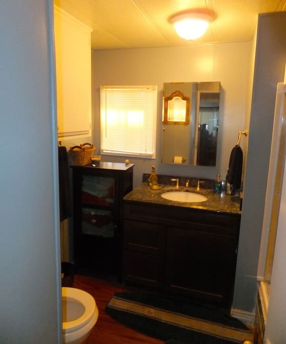 The bathroom has been remodeled with granite vanity.