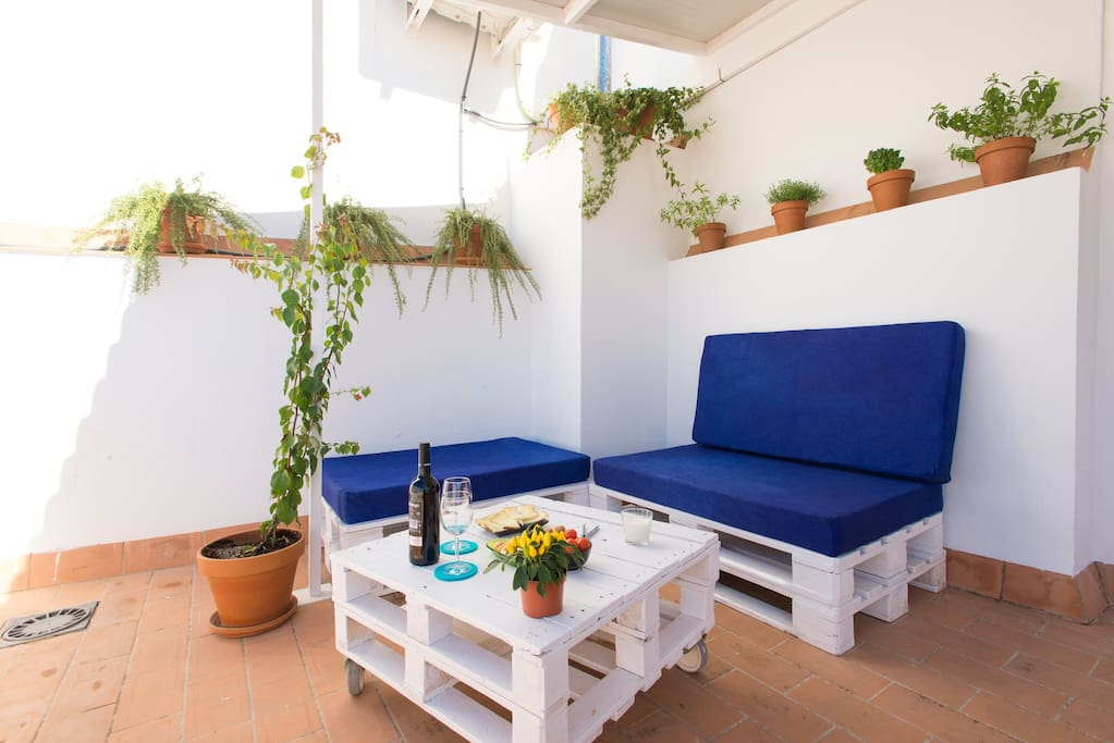 Terraza chill out con sofás de pallets contornado de plantas aromáticas (romero, albahaca, hierba luisa, menta, tomillo…),