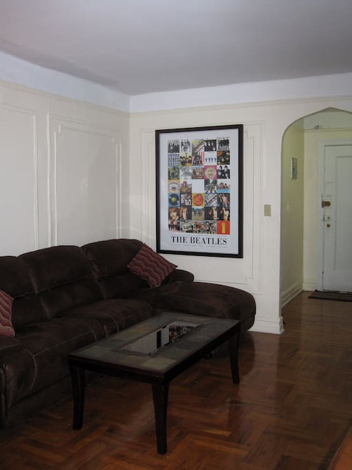 Couch with mini chaise & coffee table with view of front doorway