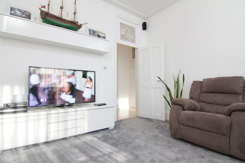 A view out into the hallway, a reclining chair and TV