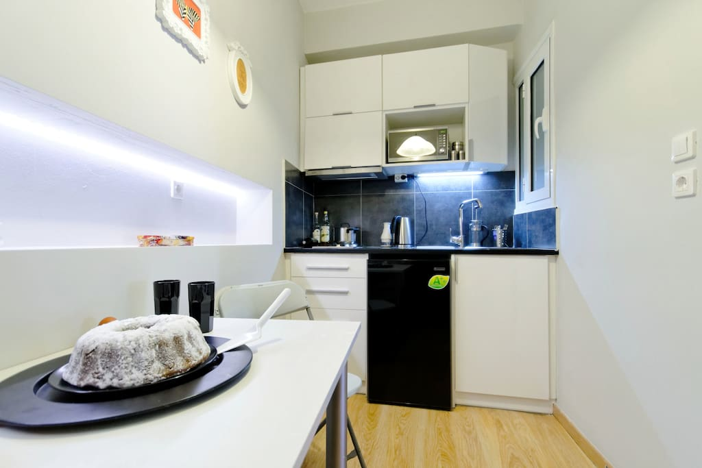 Kitchen with refrigerator cutlery , kettle , microwave, stove, glasses etc