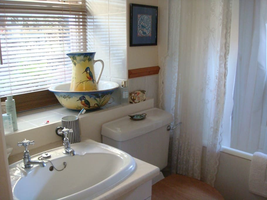 Small bathroom with electric shower and bath